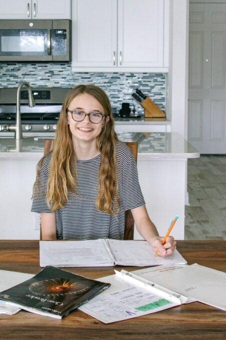 Ashling smiling while doing homework