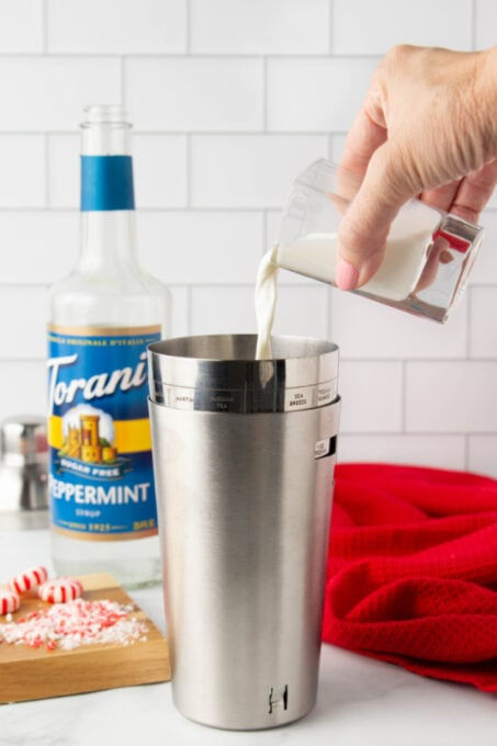 Pouring Christmas cocktail ingredients into a shaker