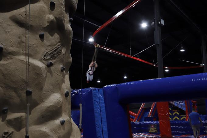 Girl riding zipline at indoor park