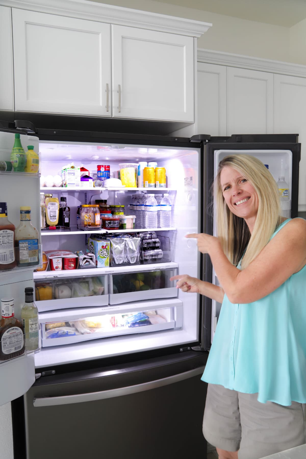 Woman pointing to the inside of a refrigerator