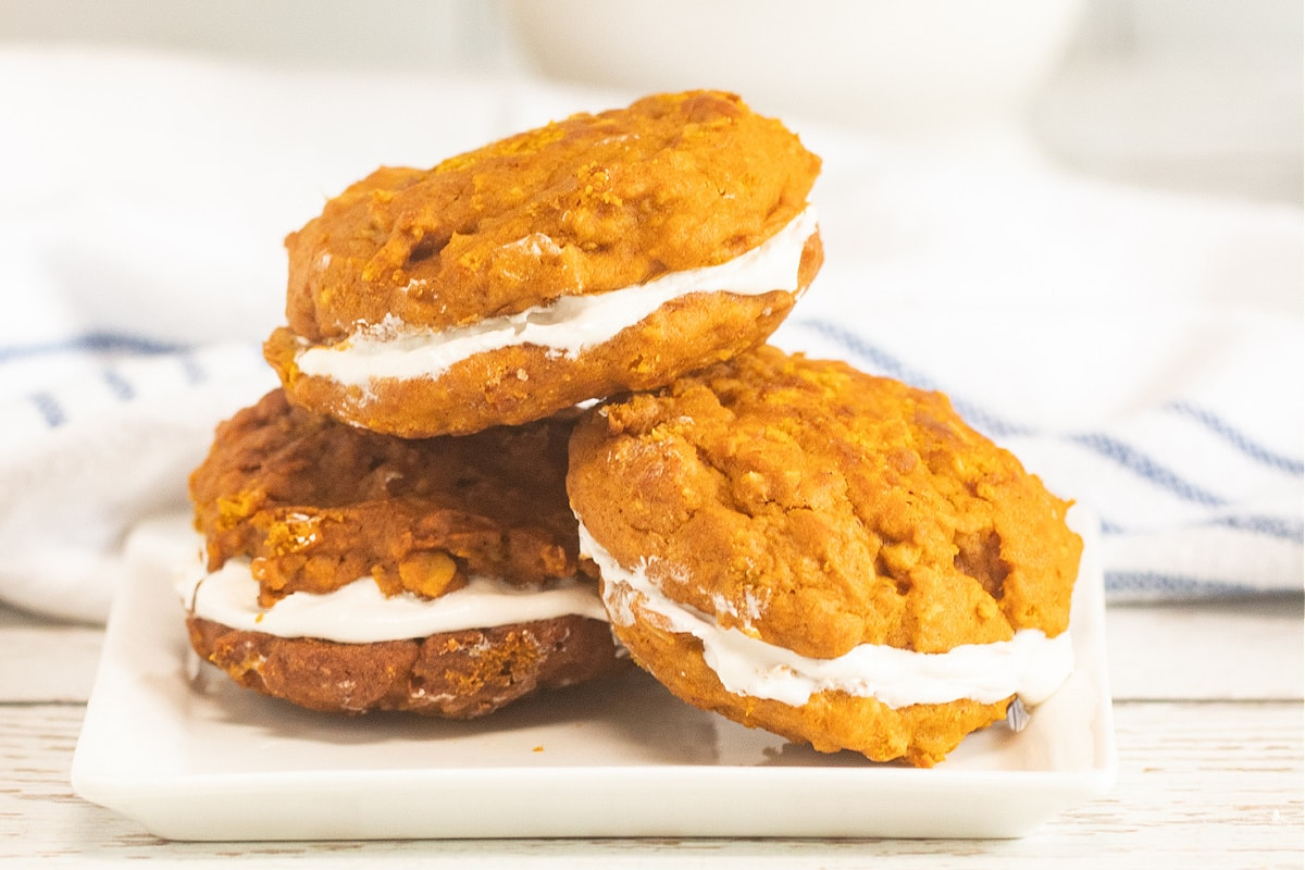 Pumpkin whoopie pies stacked on white plate