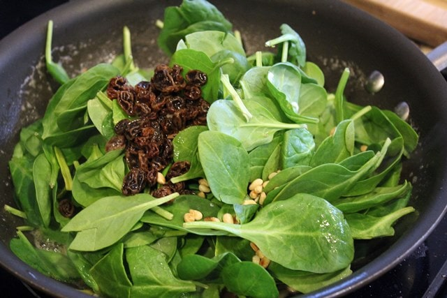 Add spinach, raisins, and pine nuts to wilt