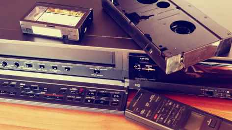black vhs on vhs player beside remote control