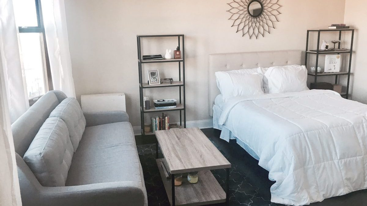 Furnished Studio with grey sofa, white bed and star mirror
