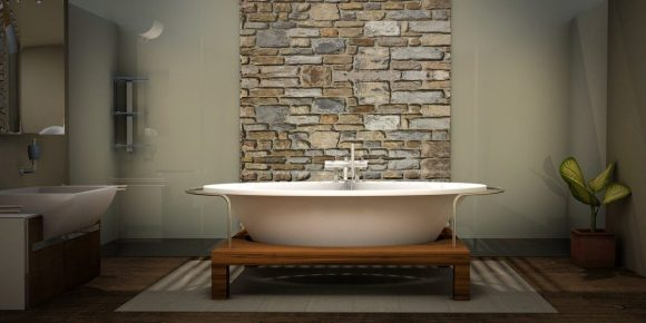 a bathtub in the center of a bathroom in front of a faux stone column