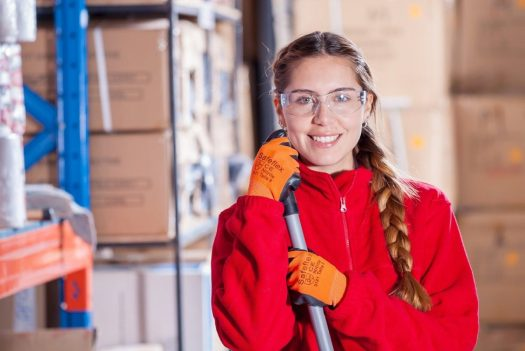 a woman wearing safety glasses and orange gloves smiles in a warehouse