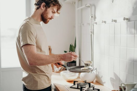 a man cooks something over a stove in a kitchen with white tile