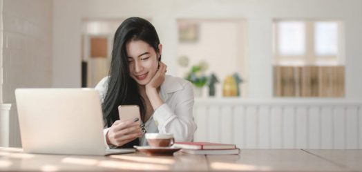 a woman with long black hair sits at a table with her laptop and coffee. she is holding her phone and smiling at it.