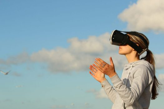 a person in a ponytail wears a virtual reality headset in front of a blue sky with clouds