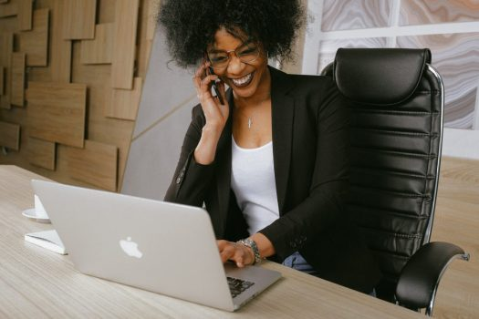 a black woman talks on the phone and smiles while working on her laptop