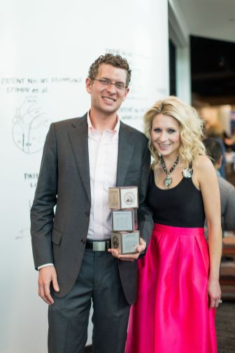 Young couple stands in front of a white board holding three square awards
