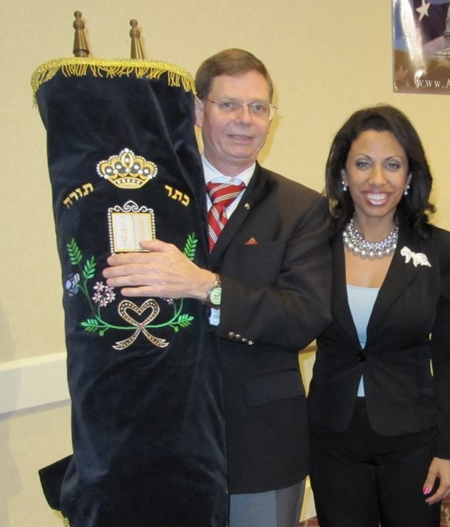 Tom Tamarkin holding a Torah with Brigitte Gabriel