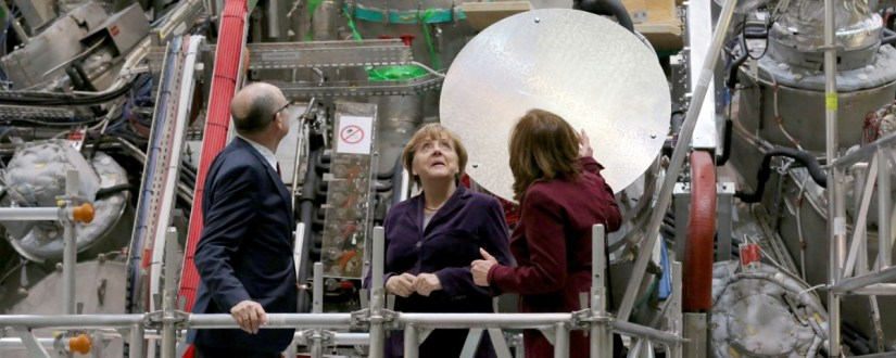 German Chancellor Angela Merkel, center, who holds a doctorate in physics, personally pressed the button at Wednesday's launch of an experiment they hope will advance the quest for nuclear fusion, considered a clean and safe form of nuclear power.