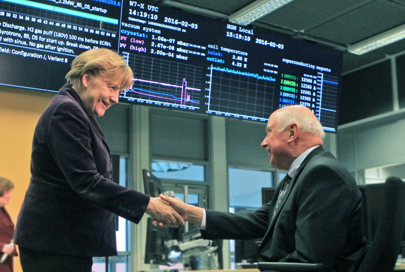 A.J. Stewart Smith, Princeton University vice president for the Princeton Plasma Physics Laboratory, and German Chancellor Angela Merkel shake hands in the Wendelstein 7-X control room at the celebration of the first hydrogen plasma. (Photo courtesy of the Max Planck Institute for Plasma Physics)