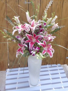 "Spectacular Stargazer lillies mingle with purple dendrobium orchids and branches of silver eucauliptus in this 16"" tall white glass vessel. Approx. 3' H."