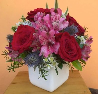 $45 half dozen red roses with pink astromerias and exotic eryngium blooms. Approx size 9x9""