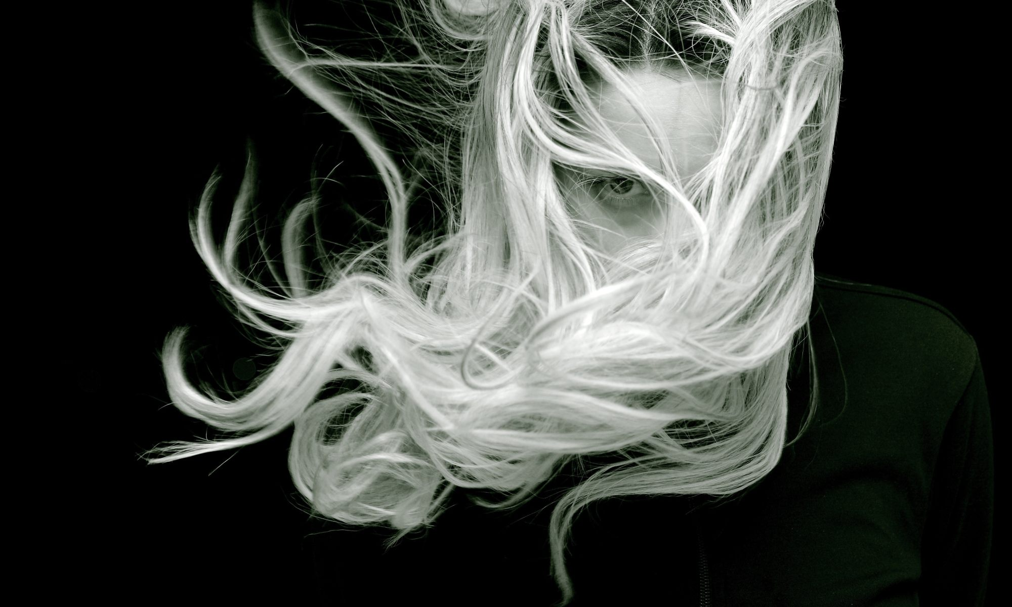 Fusion opening hours black and white portrait of lady with blonde hair being blown