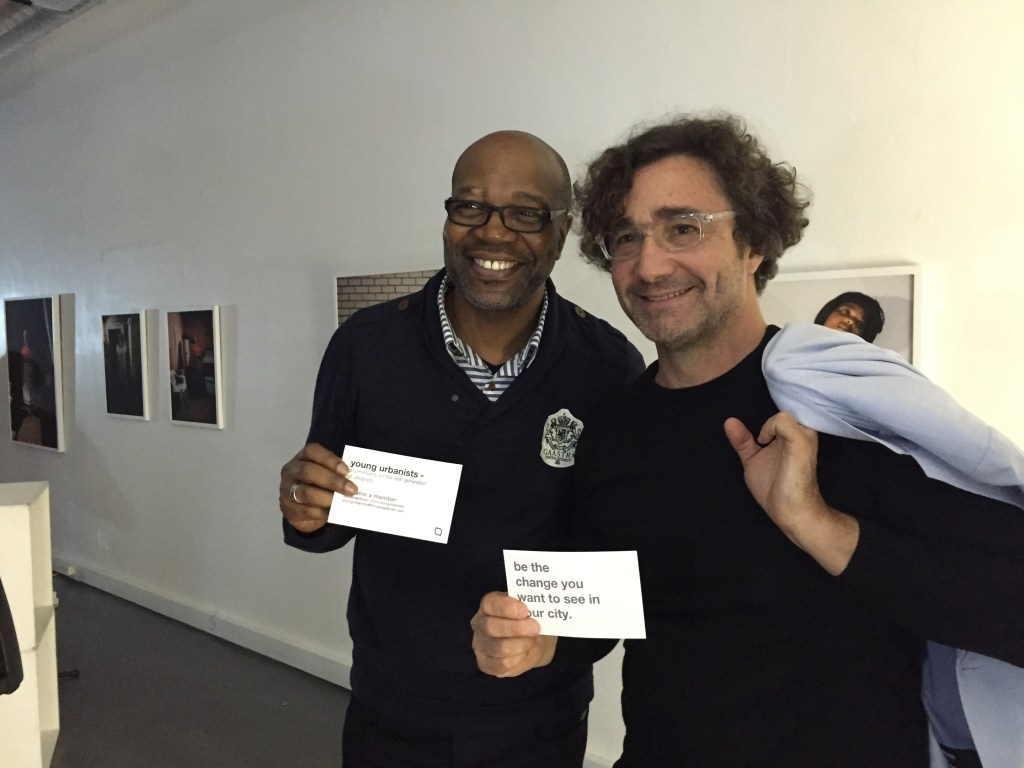 Alfredo Brillembourg (right) and Luyanda Mpahlwa (left) hold the Young Urbanists postcards.