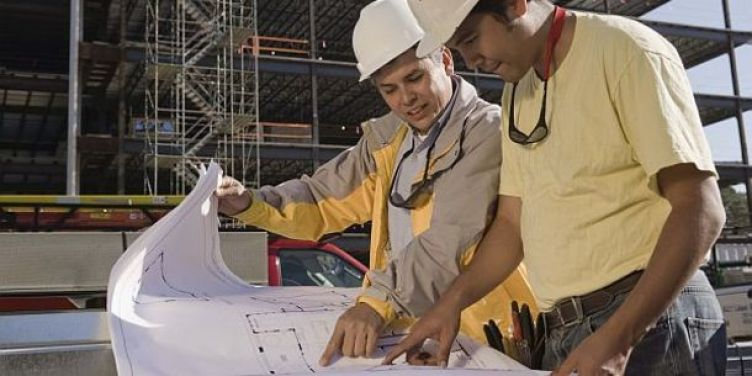 Construction workers with blueprints at construction site