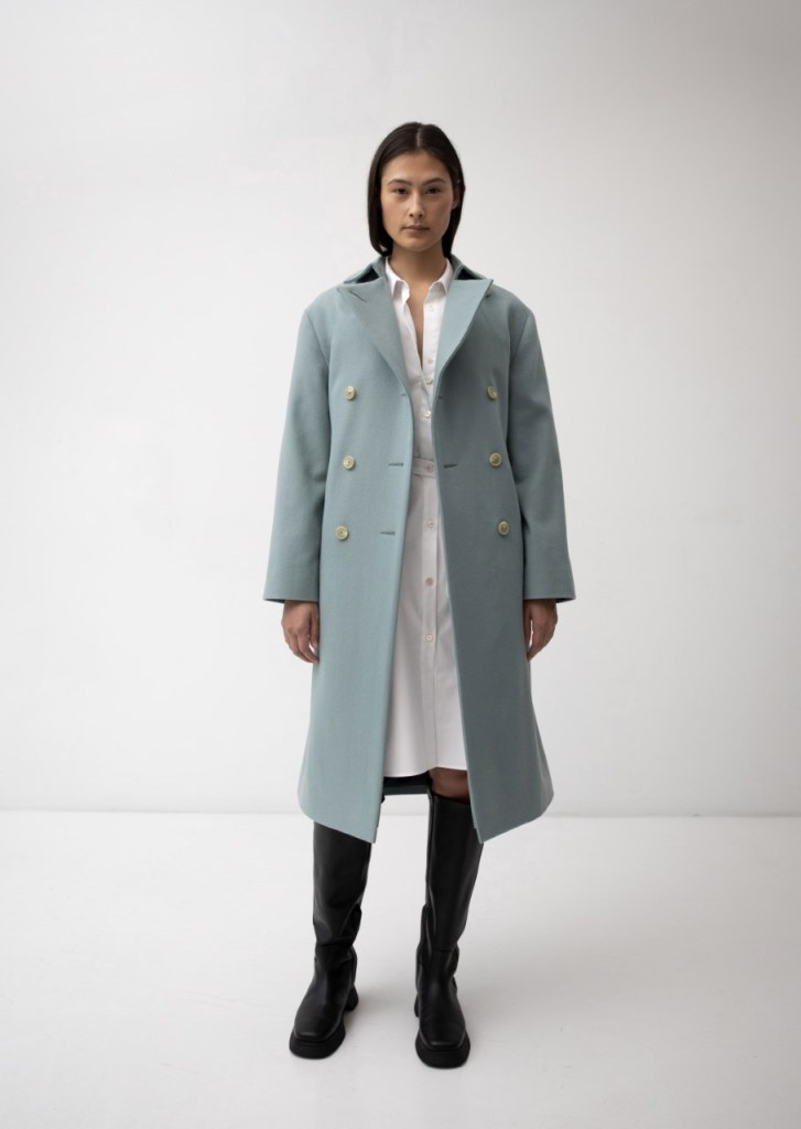 Model wears a pale green trench coat with white double breasted buttons by The Array