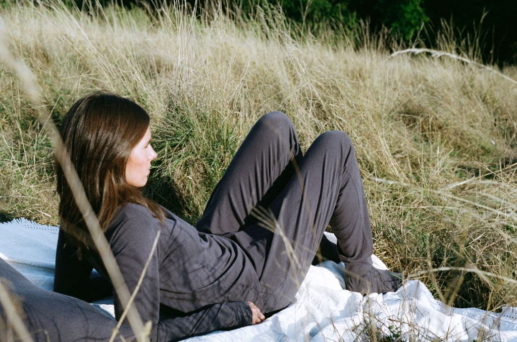 Model wears dark grey long-sleeve top, trousers and socks while lying on a blanket in a field