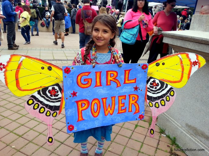 Little girl with Girl Power sign with homemade butterfly wings