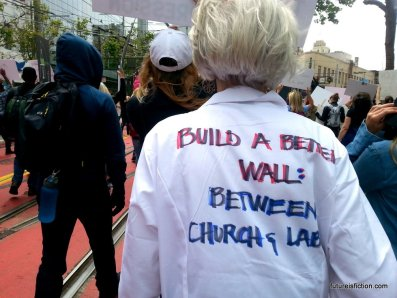 Woman's lab coat reads: BUILD A WALL BETWEEN CHURCH AND LAB.