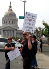 "A protest sign with ""Keep your TiNY hands off science funding!"" where TiNY are elements from the periodic table."