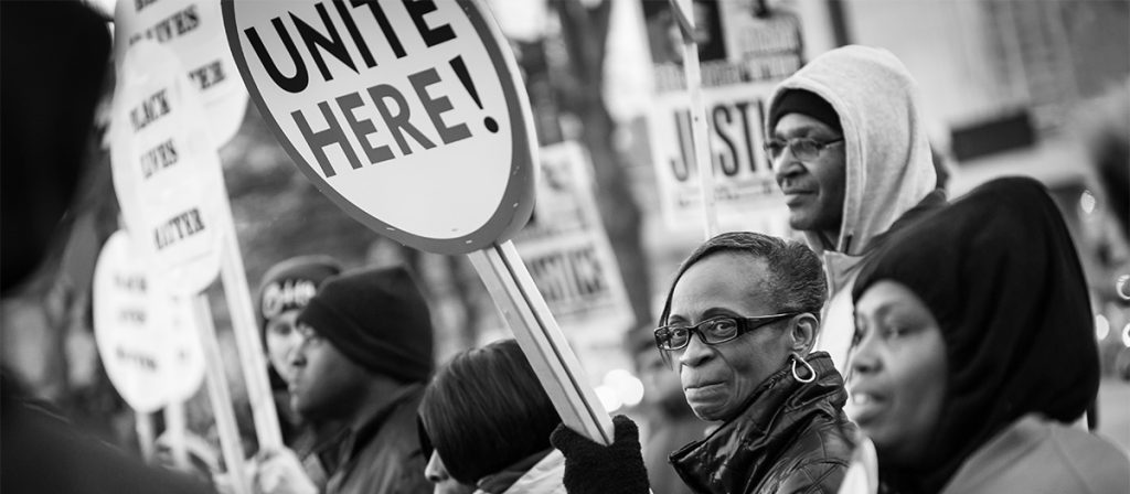 """Photo of protestors holding signs. Image is focused on African American woman holding a sign that says, """"Unite Here!"""""""