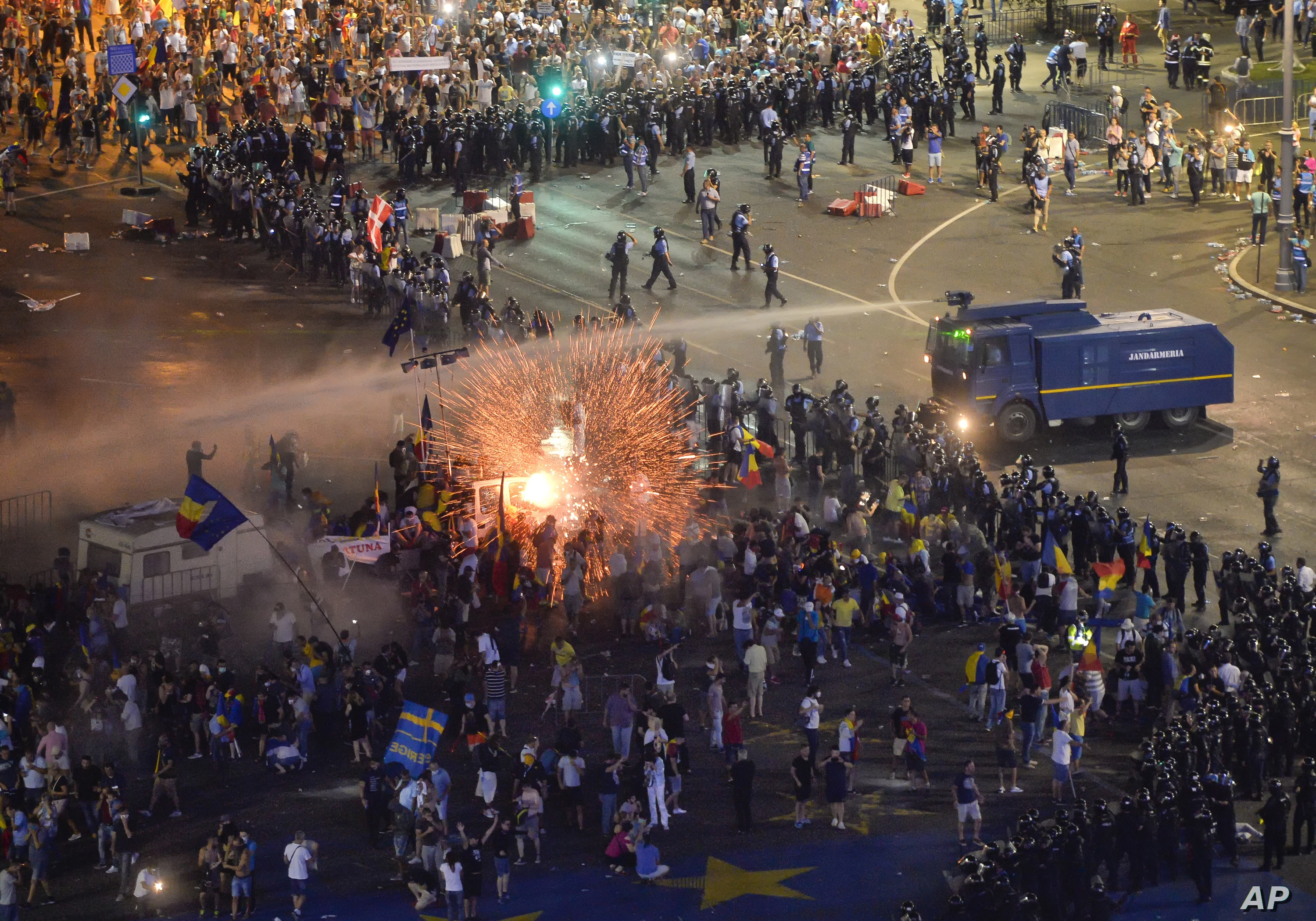 a teargas canister explodes as riot police charge using canon to clear the square during protests outside the government headquarters in Bucharest, Romania.