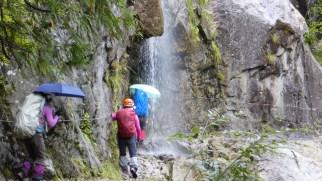 傘をさして沢シャワーを通過