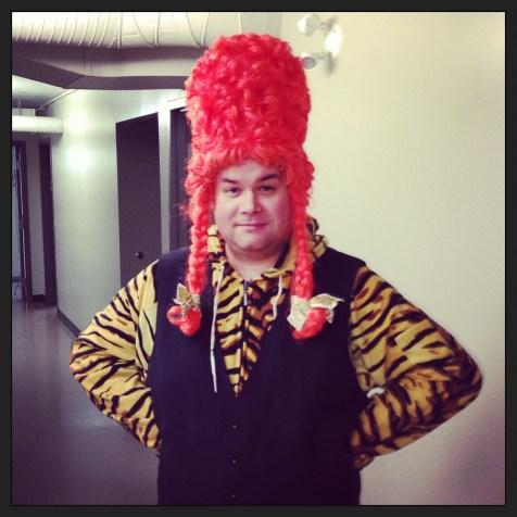 """Dame Olga"" (Cory Jenkins) is fierce in her (his?) tiger print onesie and wig."