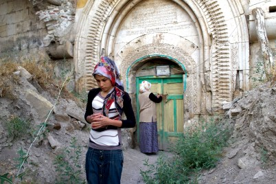 A woman stands in the foreground of a monastery in Armenia, walking away while another woman stands in front of the door, possibly locking it up. The Monastery is built into a cliffside, and the rocks and stones are beginning to crumble.