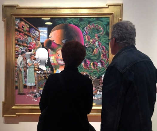 A man and woman stand with their back to the viewer examining a work of art on display.