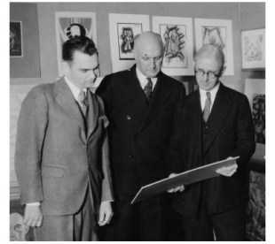 Karl Bolander stands on the left viewing student artwork with two other men.