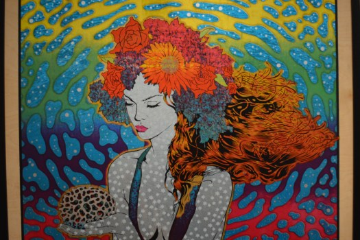 A woman with red hair and a floral headband holds a coral. The pattern of the coral is reflected behind her in psychedelic colors of the rainbow.