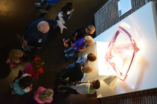 A school group, led by FWMoA Docent Michael Greene, gazes at a glass sculpture by Peter Bremers.