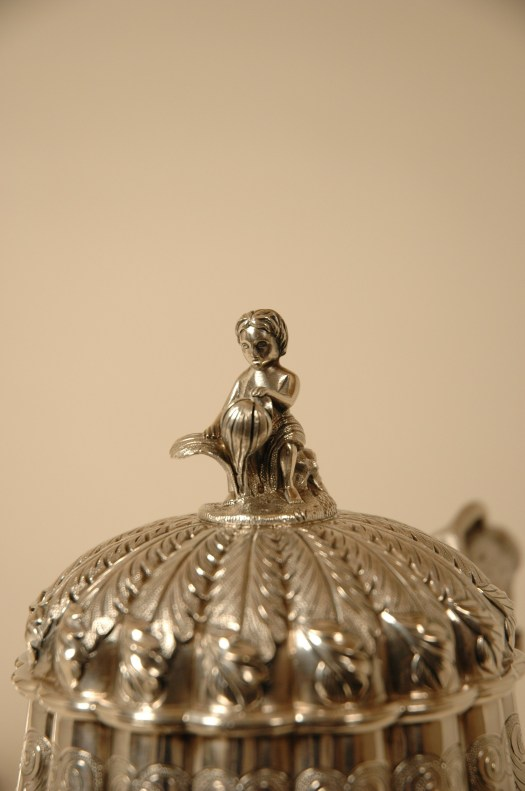 This close-up shows the details on the lid of one of the pieces in the set, a girl sits atop it.