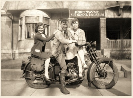 Three students, one male and two females, sit on a motorcycle in front of the original Fort Wayne Art School & Museum.