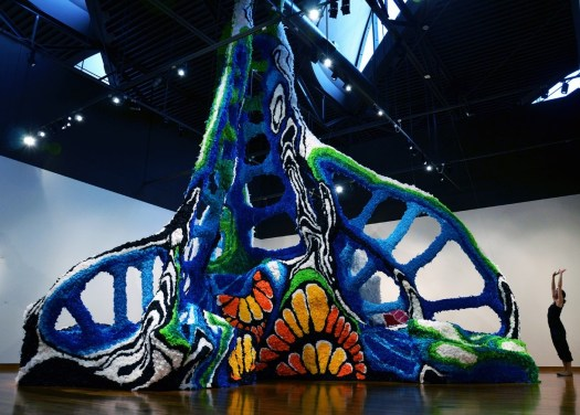 Artist Crystal Wagner stands next to her large-scale installation at FWMoA. Abstract, the sculpture uses multiple colors to construct a spire that nearly touches the ceiling.