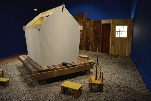 An installation by Johnny Coleman features a house on a pallet, with stools around it.