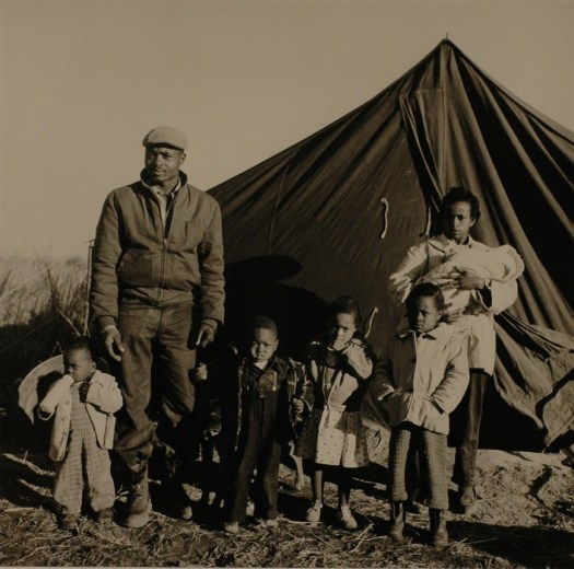A Black family, father, mother, and five children, stand in front of a tent outside after being evicted from their house.