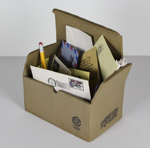 A sculpture of a cardboard box, open, that contains letters with writing and postmarks and a pencil.
