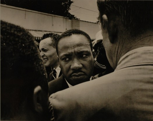 Martin Luther King, Jr.'s face is framed by the shoulder of a male FBI agent as he walks through the crowd.