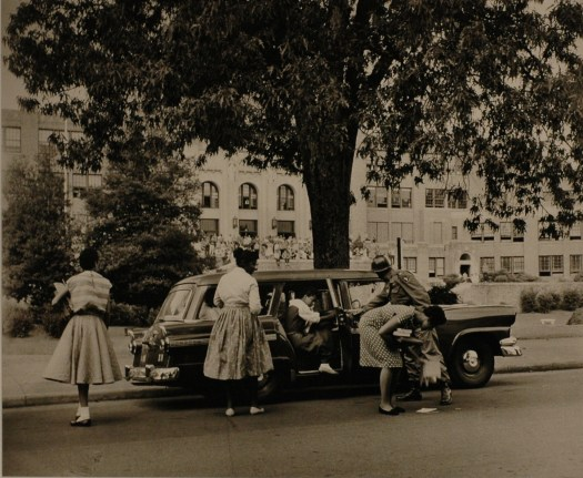 The Little Rock Nine exit the car on the street parked outside their school. In front of the school is group of people protesting with signs. A tree in front bisects the group, and we can see one student spilling her books and papers as a policeman helps another out of the car.