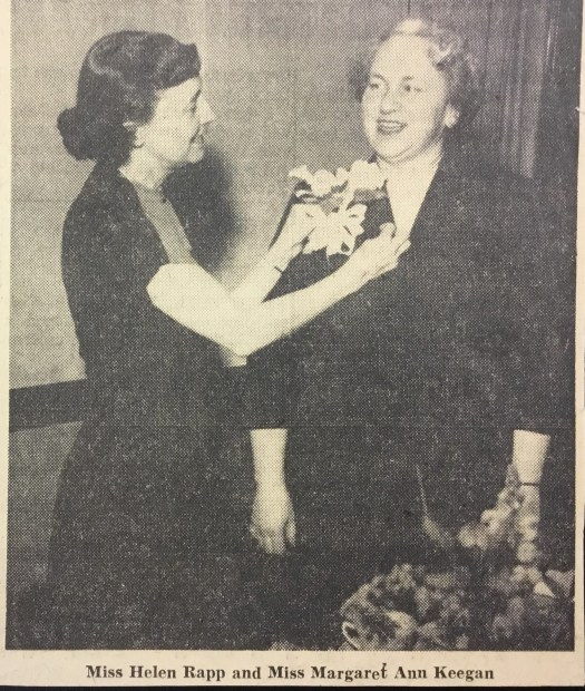 Mrs. Helen Rapp and Mrs. Keegan stand next to each other as Mrs. Rapp pins a flower to Mrs. Keegan's jacket.