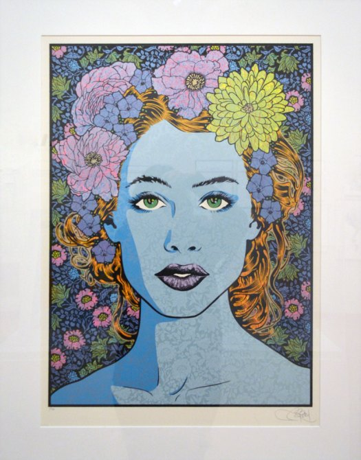 A portrait of a woman with blue, flower patterned skin. She has orange hair and wears flowers in her hair, which is pulled back from her face. Her green eyes stare at the viewer straight on, and are brightened by the floral wallpaper that makes up the background.