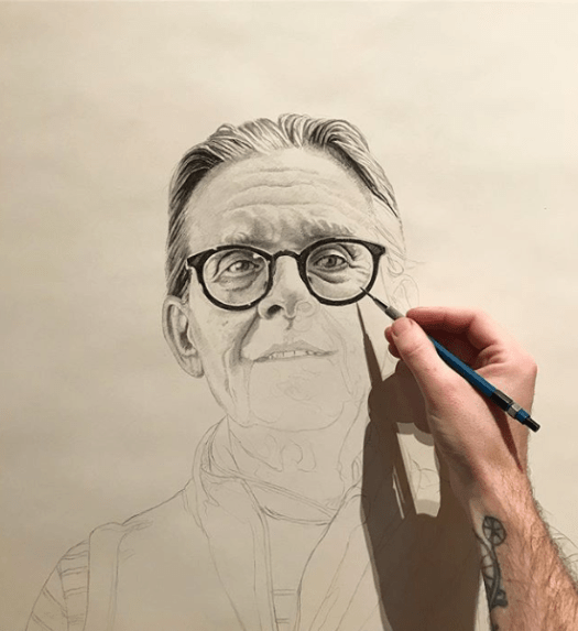 The drawing of Suzanne takes shape. The artist has drawn in her hair, the top of her face, and her glasses while the rest of her remains in sketches, waiting to be completed.