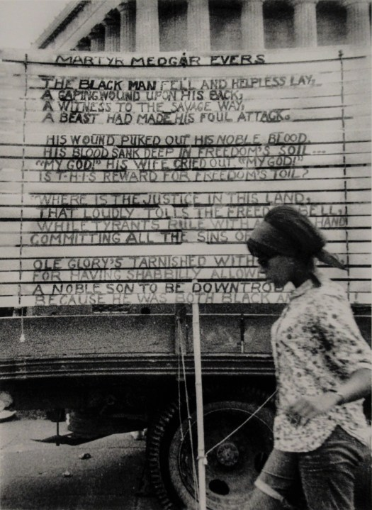 This black and white photo shows a woman walking alongside a car. Attached to the car is a poem, written on window blinds, to Civil Rights activist Medgar Evers. In the background is a large, white building with colonnades.