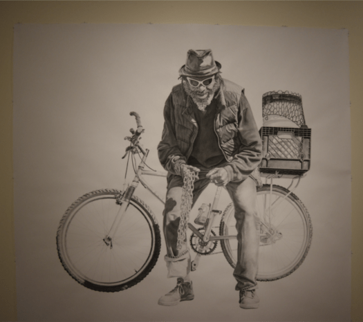 """This life-size portrait, done in charcoal, shows """"Blue"""" holding his bike chain, his bike behind him. He wears a hat, sunglasses, puffer jacket over a sweatshirt, and rolled up jeans. His bike has a basket on the back with miscellaneous objects in it."""